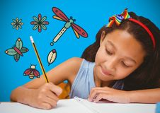 Girl writing in front of blue blank background with magical nature graphics Stock Photos