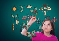 Girl writing in front of green blank background with magical nature graphics Royalty Free Stock Photos