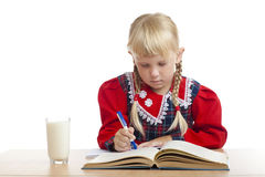 Girl writing and a glass of milk Stock Image