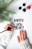 Girl writing Happy new year calligraphy card Royalty Free Stock Photos