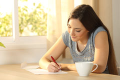 Girl writing a letter on a table. Happy girl writing a letter on a table at home Royalty Free Stock Image