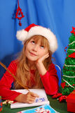 Girl writing a letter to santa. Young girl in santa`s hat writing a letter to santa  by golden feather pen Royalty Free Stock Images
