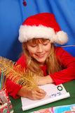 Girl writing a letter to santa. Young girl in santa`s hat writing a letter to santa  by golden feather pen Stock Images