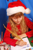 Girl writing a letter to santa. Young girl in santa`s hat writing a letter to santa  by golden feather pen Royalty Free Stock Photos