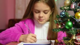 Girl writing a letter to Santa Claus, the focus is on the fur-tree in front of her stock video footage