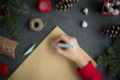 Girl writing letter to Santa with ink pen on yellow paper on grey background with christmas decorations. Overhead view Royalty Free Stock Photo
