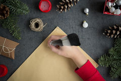 Girl writing letter to Santa with ink pen on yellow paper on grey background with christmas decorations. Overhead view Stock Images