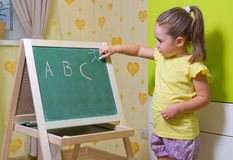 Girl writing letters on blackboard Royalty Free Stock Photo