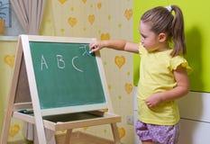 Girl writing letters on blackboard Royalty Free Stock Photo
