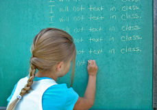 Girl writing lines on chalkboard Stock Photos