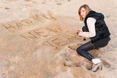 Girl Writing New Year in Sand Stock Images