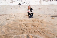 Girl Writing New Year in Sand Royalty Free Stock Photo
