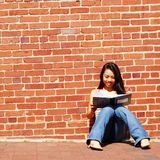 Girl Writing In Note Book. Girl writing in notebook in the city Royalty Free Stock Image