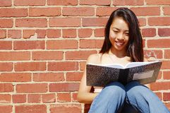 Girl Writing In Note Book. Girl writing in notebook in the city Stock Photo
