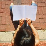 Girl Writing In Note Book. Girl writing in notebook in the city Royalty Free Stock Photo