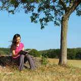 Girl Writing in Note Book. Girl writing in notebook in a field Royalty Free Stock Photography