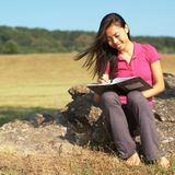 Girl Writing in Note Book. Girl writing in notebook in a field Stock Photo