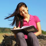 Girl Writing in Note Book. Girl writing in notebook in a field Stock Images