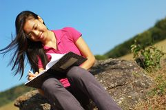 Girl Writing in Note Book. Girl writing in notebook in a field Royalty Free Stock Images