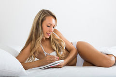 Girl writing in notebook in bed Royalty Free Stock Images