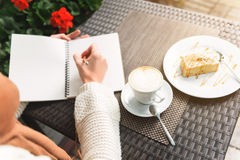 Girl writing into notebook in cafe Stock Images