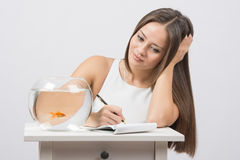 Girl writing in a notebook desire to fulfill a goldfish Stock Photo