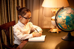 Girl writing in notebook at desk with globe Stock Photography