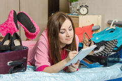 Girl writing in a notebook, going on a trip Stock Photo
