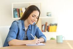 Girl writing in a notebook at home stock photos
