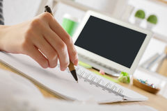 Girl writing in notepad. Close up of girl writing in notepad placed on wooden desktop with blank laptop, supplies and other items. Mock up stock photography