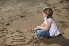 Girl writing number in the sand Stock Photo