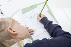 Girl writing numbers on paper at table Stock Photography