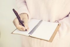 Girl writing with pen in blank diary Royalty Free Stock Photo