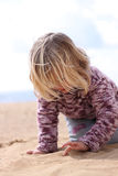 Girl writing in the sand. A little girl writing in the sand. Soft focus front and back Royalty Free Stock Images