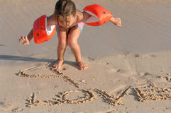 Girl writing in sand Royalty Free Stock Photos