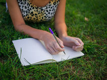 Girl writing something and lying on the grass in the summer park. Girl writing something, lying on the grass in the summer park royalty free stock image