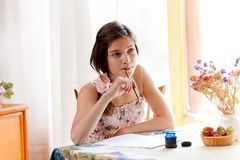 Girl writing at table by pen Royalty Free Stock Image