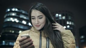 The girl is writing text on a smartphone in the background of a night city. Close-up stock video footage