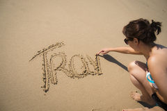 Girl writing the word travel in the sand Stock Photo