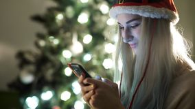 Girl written on a phone and smiling on christmas Stock Images