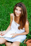 Girl writting in a notebook sitting in the grass Stock Photography