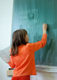Girl writting on the school board. Girl in the front on the green board Royalty Free Stock Photography