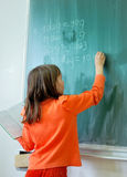 Girl writting on school board. A little girl writting and drawing on the green board Stock Image