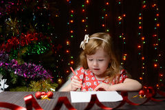 Girl wrote in red pencil a letter to Santa Claus Stock Image