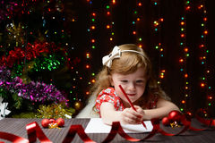 Girl wrote in red pencil a letter to Santa Claus Royalty Free Stock Photography