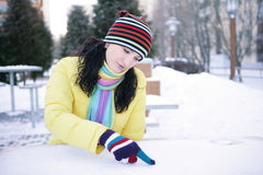 Girl wrote in the snow. Beautiful girl in a yellow jacket, wrote in the snow in a street caf Royalty Free Stock Photo