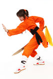 The girl wushu in orange costume in low guard. Carries out a complex martial arts royalty free stock photography