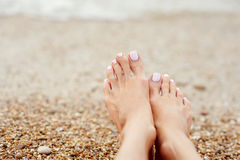 Girl& x27; pierna de s en los guijarros coloridos la playa por el mar Foto de archivo libre de regalías