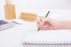 Girl's hand writing in notepad Royalty Free Stock Images