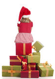 Girl with xmas hat seated presents Stock Image